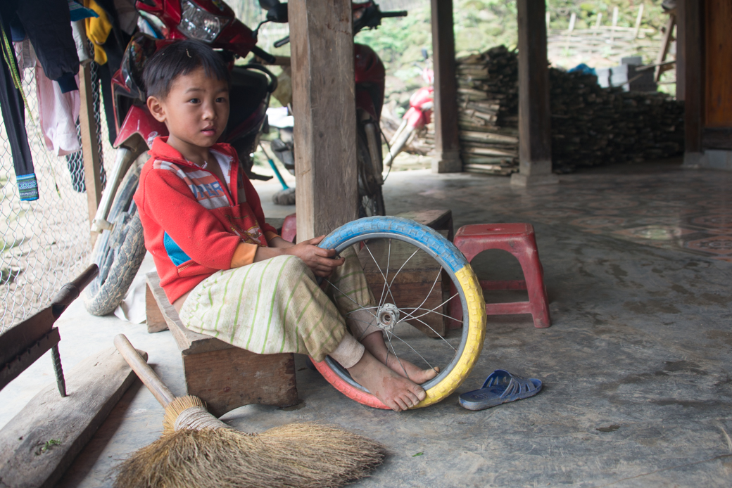 Asian boy with bicycle wheel