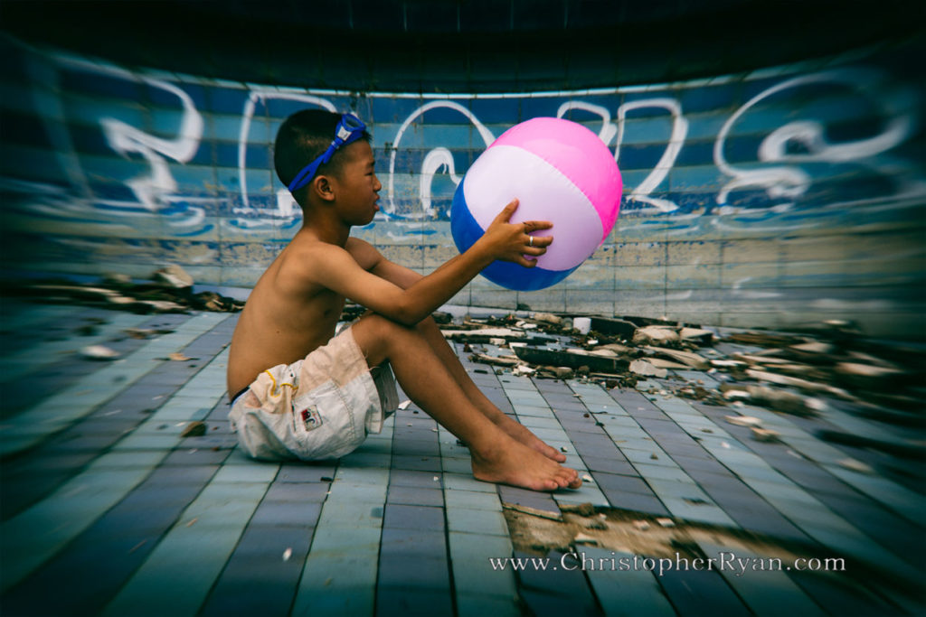 shirtless boy in abandoned swimming pool