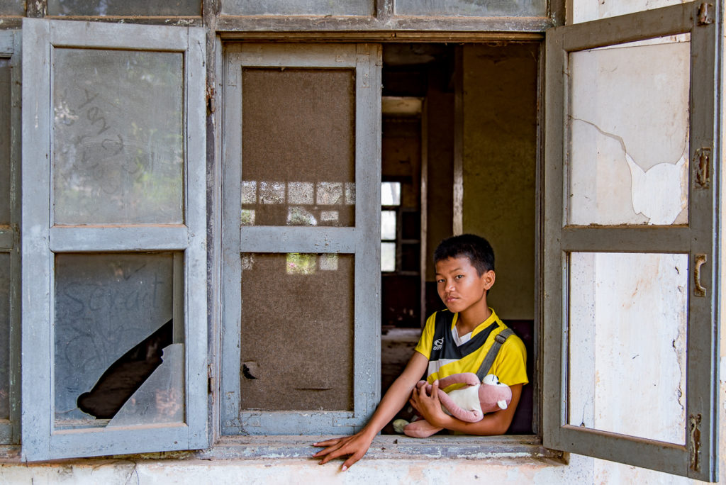 Boy in abandoned hotel Vientiane