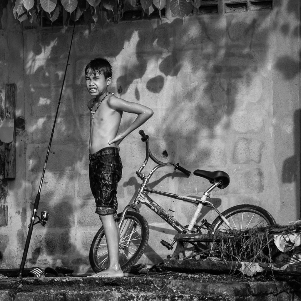 a wet shirtless boy with bike and fishing pole.