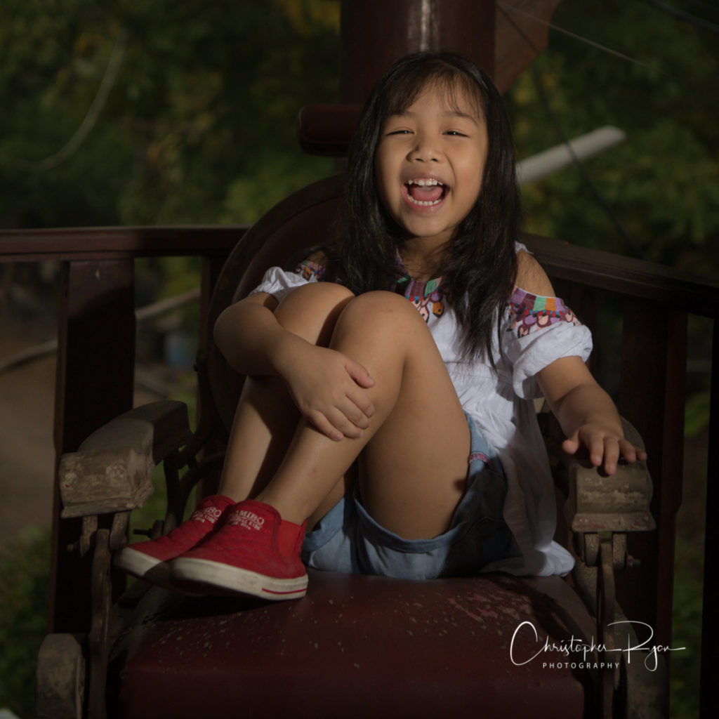 adorable little girl in red sneakers on antique barber chair