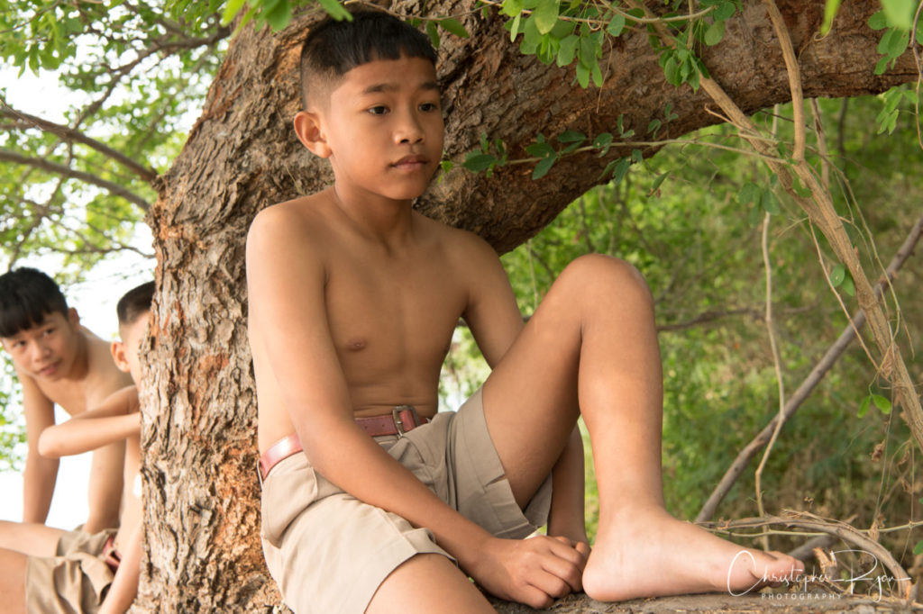 barefoot boy in a tree
