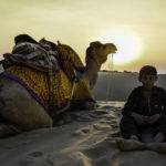 barefoot 10 year old indian boy in the desert with camel