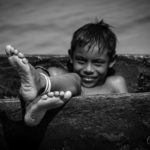barefoot kuna indian boy on a boat from focus on feet project with kids feet