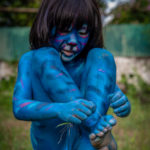 barefoot boy bodypainted in the style of a blue tiger