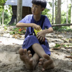 barefoot 10 year old boy playing in a sandbox