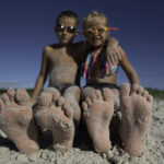 brother and sister at beach with sand on their bare feet