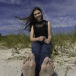 sexy barefoot teen girl on the beach showing her soles