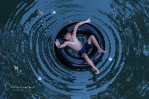 shirtless boy on inner tube in a river