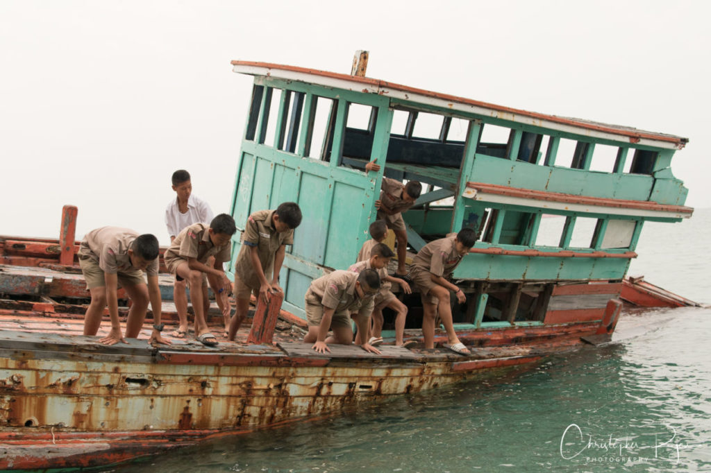 thai boy scouts on an abandoned fishing boat