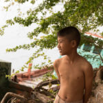 shirtless boy with abandoned boat in the background
