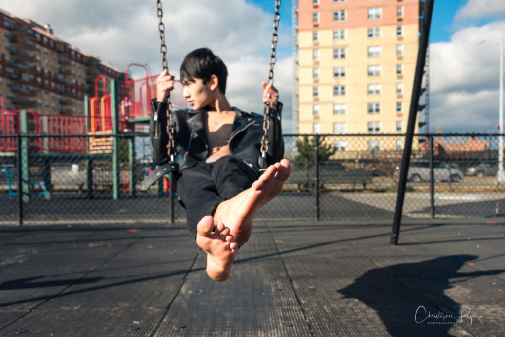 barefoot boy on a swing at rockaway beach in new york city
