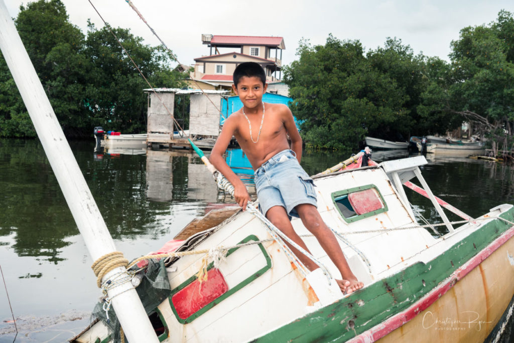 shirtless boy in jean shorts playing on an old boat