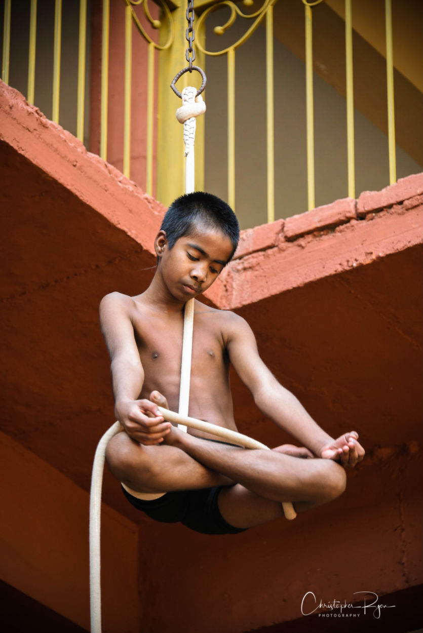 young shirtless 13 year old athletic boy in namaste pose on mallakhamb rope