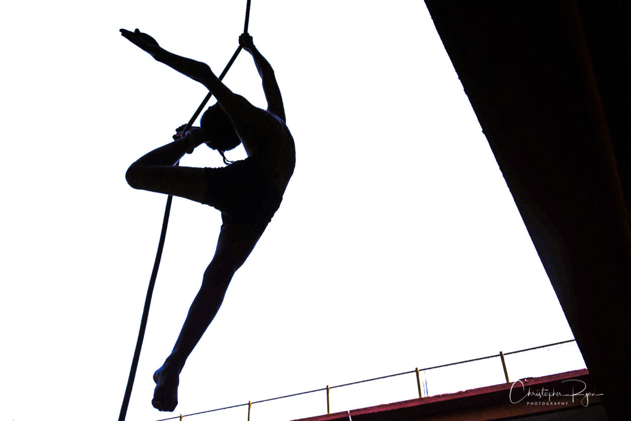 silhouete of a beautiful shirtless athletic boy performing aerial arts