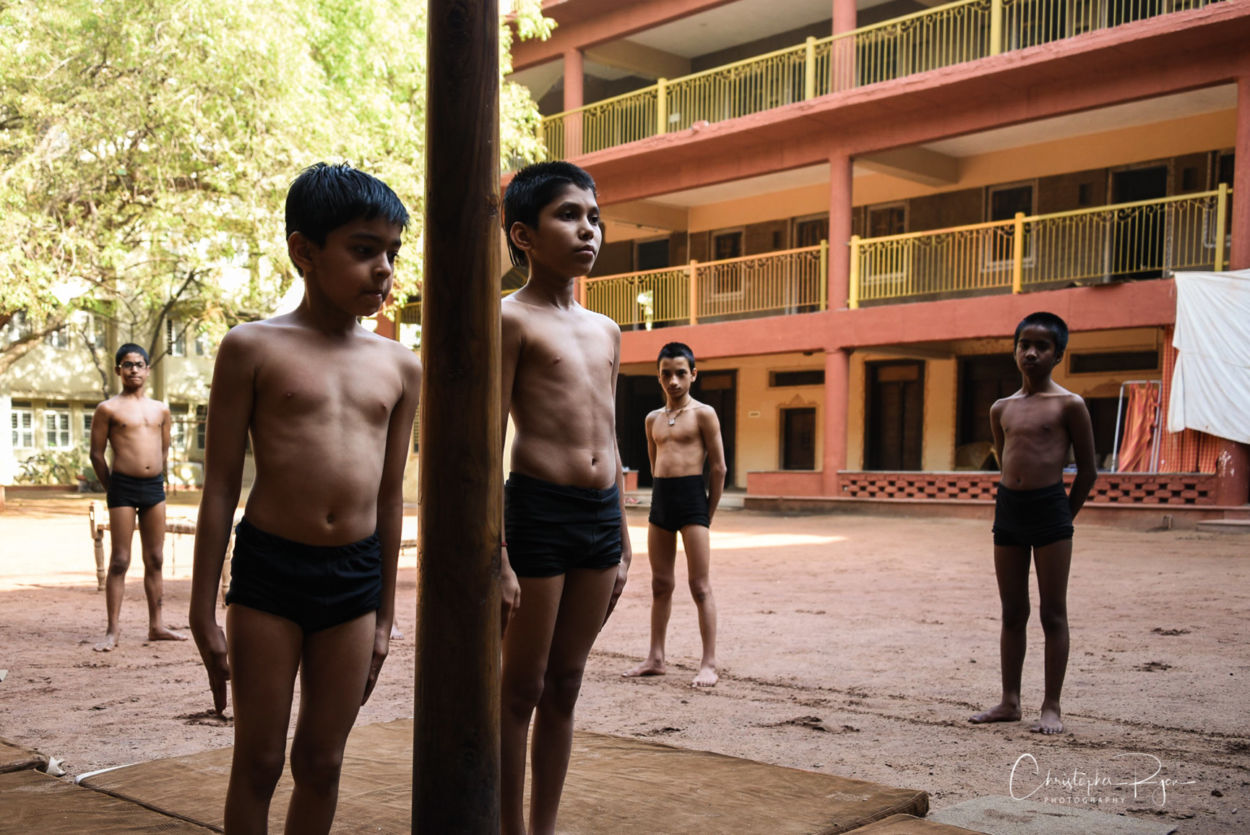 Shirtless athletic indian boys standing next to mallakhamb pole in ahmedabad india