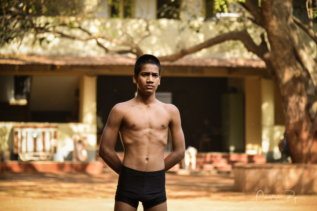 15 year old boy with defined body watching mallakhamb performers