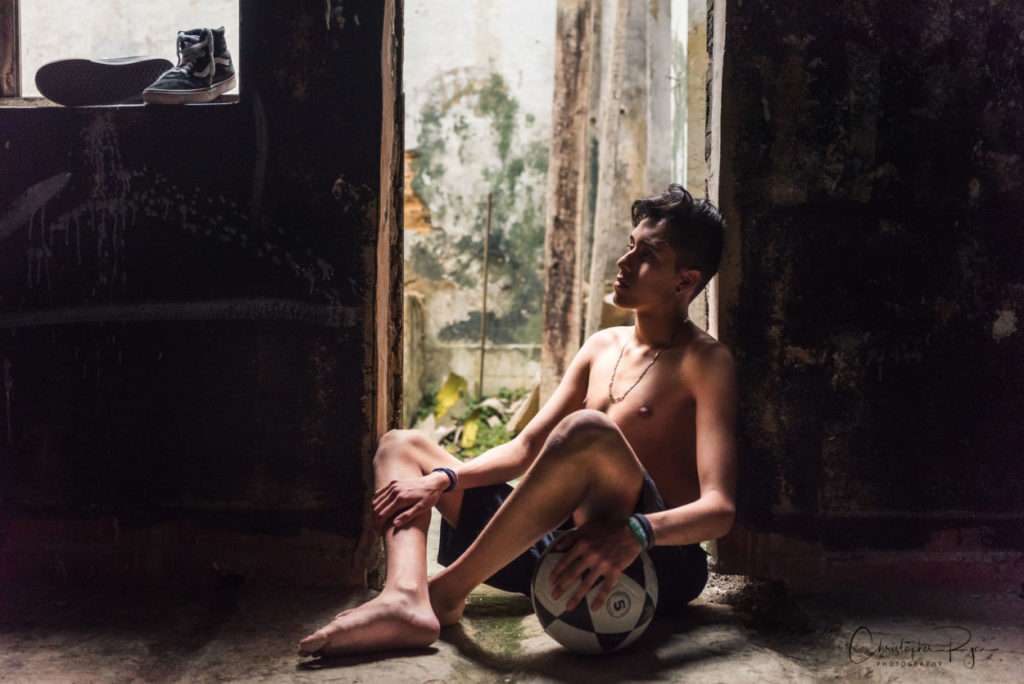 shirtless and barefoot teen with soccer ball.