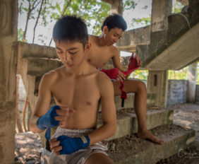 Teenage boys taping their hands before a Muay Thai fight