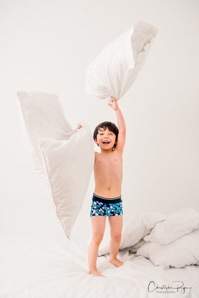 five year old boy in blue underwear playing with pillows