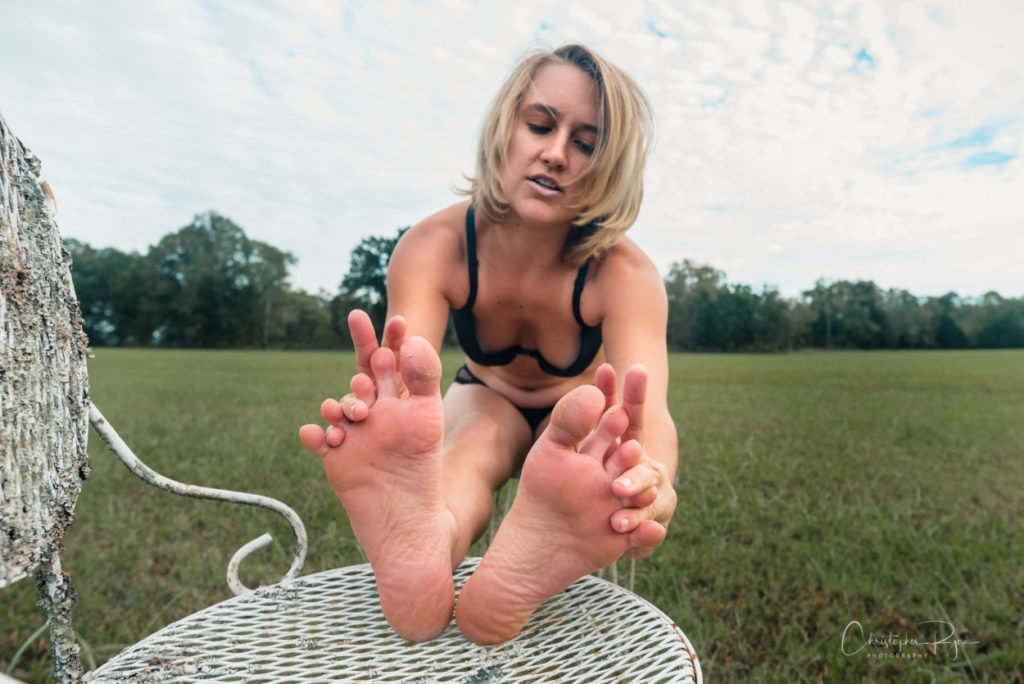 sexy blond girl playing with her bare feet.