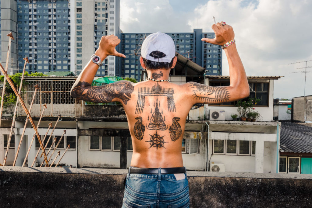 back of thailand teenager with Buddhist tattoos