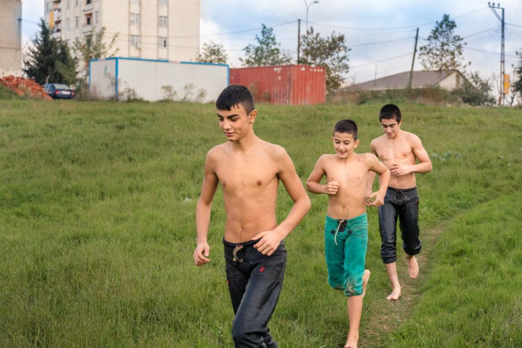 shirtless boys running through a field
