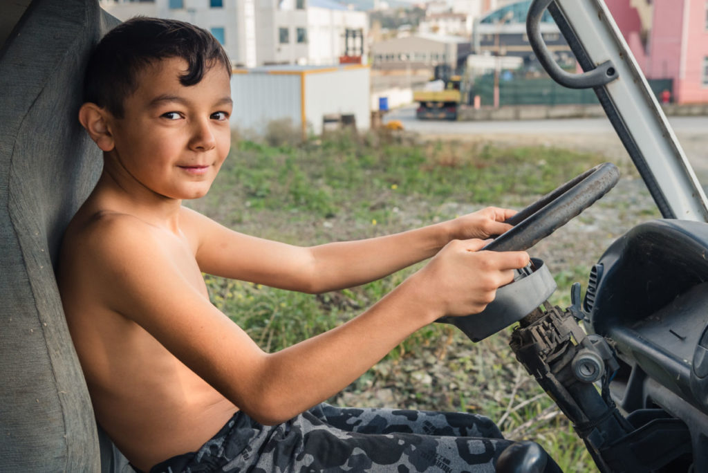 shirtless boy playing in a junked truck in a scrapyard in Turkey