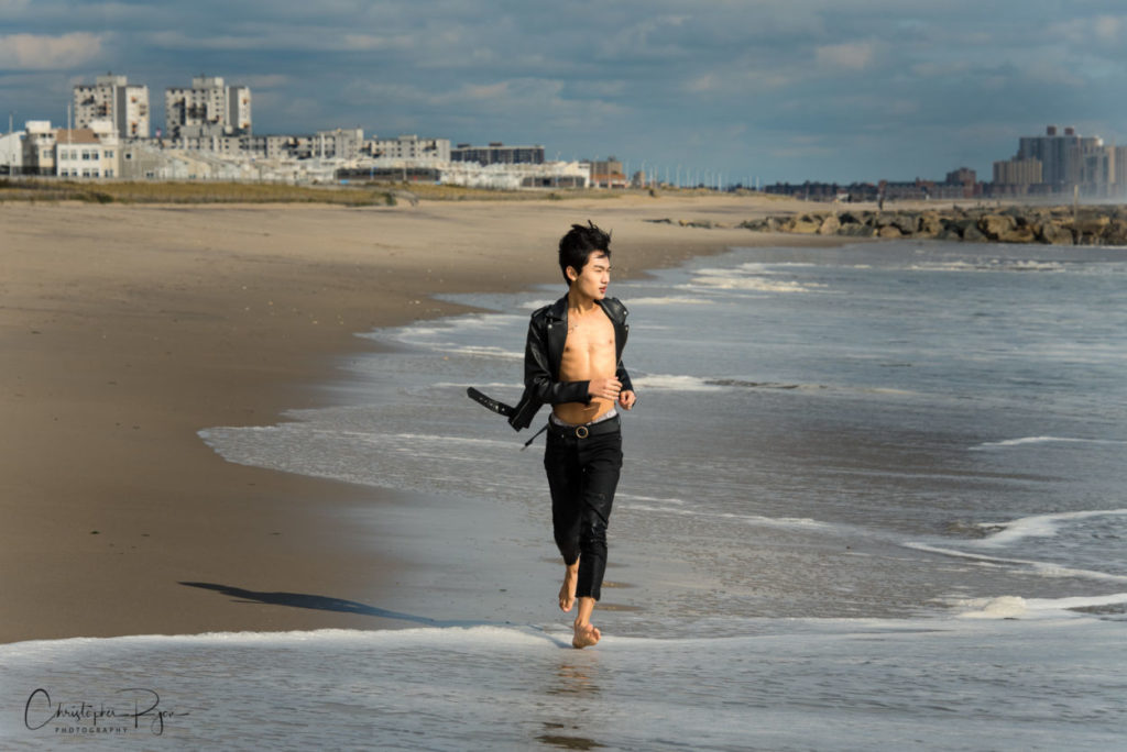 barefoot teen boy in open leather jacket and no shirt running on the beach in New York