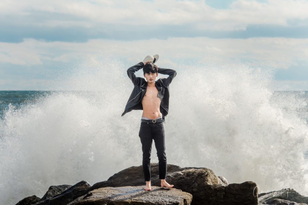 asian boy standing on rock jetty with huge wave behind him