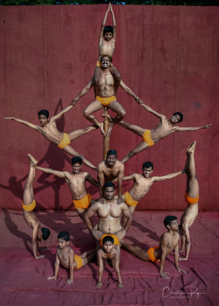 shirtless male mallakhamb performers demonstrating an intricate pose in Mumbai, India