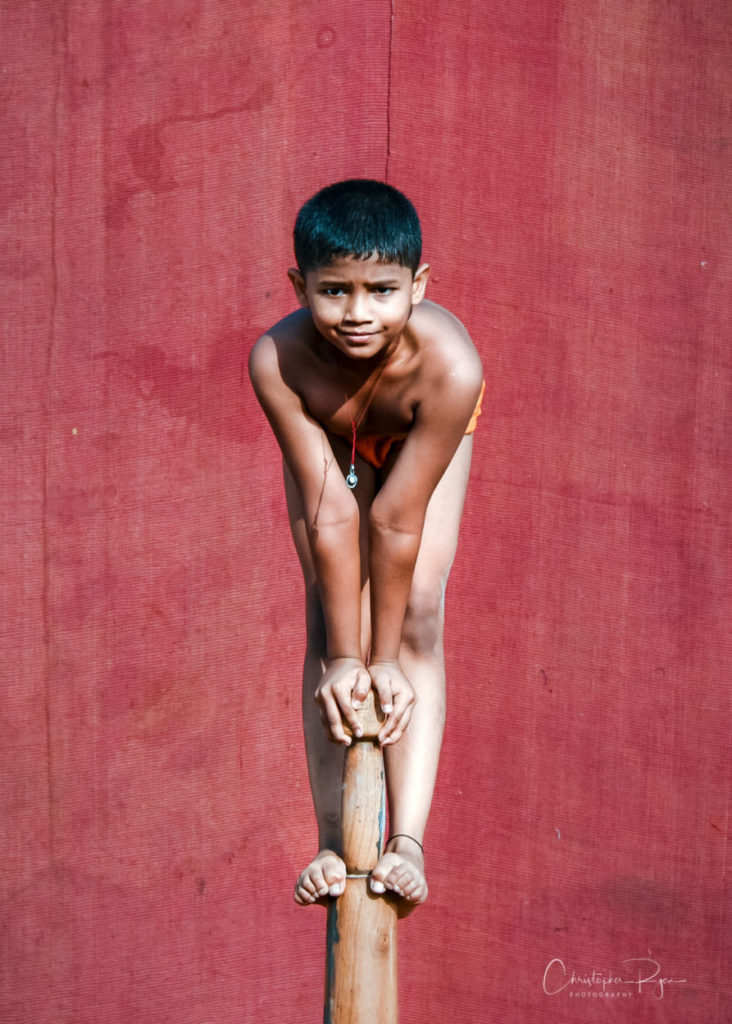 Young shirtless mallakhamb performer boy preparing to demonstrate another beautiful pose