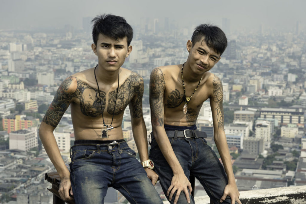 two shirtless boys in bluejeans and tattoos on top of a skyscraper