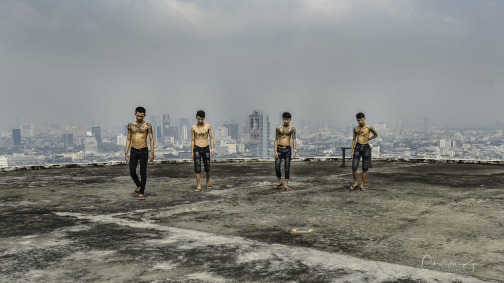 group of shirtless boys on the roof of a skyscraper